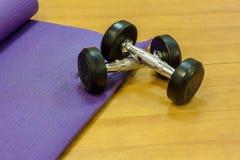 Pesas de gimnasia del equipo de la aptitud, estera de la yoga, en el fondo de madera Foto de archivo