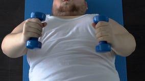 Pesas de gimnasia de elevación del hombre gordo débil de los músculos para arriba con esfuerzo que miente en piso, aptitud almacen de video