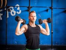 Pesas de gimnasia de elevación del hombro del entrenamiento del hombre joven Fotografía de archivo
