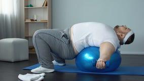 Pesas de gimnasia de elevación del soltero gordo perezoso en hogar de la bola, la falta de fuerza y la resistencia almacen de video