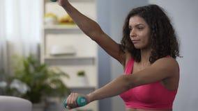 Pesas de gimnasia de elevación de la mujer atractiva, forma de vida activa, ejercicio físico, aptitud almacen de video