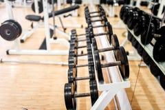 Pesas de gimnasia en club de deportes, gimnasio o centro de aptitud moderno Imágenes de archivo libres de regalías