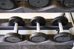 Pesas de gimnasia en club de deportes moderno Imagen de archivo libre de regalías
