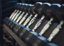 Pesas de gimnasia en un estante foto de archivo