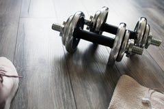 Pesas de gimnasia en un piso de madera Imágenes de archivo libres de regalías