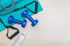 Pesas de gimnasia, equipo del ejercicio, estera de la yoga del gimnasio, y botella de wate foto de archivo