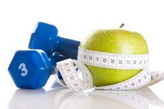 Pesas de gimnasia, manzana verde fresca y cinta de la medida Imagen de archivo