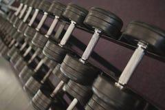 Pesas de gimnasia negras pesadas en el estante en sitio de pesos fotografía de archivo