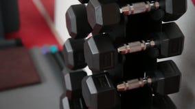 Pesas de gimnasia para la mentira de entrenamiento en el estante en el gimnasio almacen de metraje de vídeo