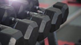 Pesas de gimnasia para la mentira de entrenamiento en el estante en el gimnasio metrajes