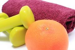 Pesas de gimnasia, toalla para usar en aptitud y fruta fresca Imágenes de archivo libres de regalías