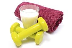 Pesas de gimnasia, toalla para usar en aptitud y vidrio de leche Imágenes de archivo libres de regalías
