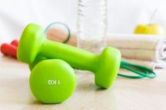 Pesas de gimnasia verdes, botella de agua, manzana, comba y una toalla Fije para los deportes Imágenes de archivo libres de regalías