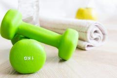 Pesas de gimnasia verdes, botella de agua, manzana y una toalla Fije para los deportes Imagen de archivo libre de regalías