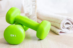 Pesas de gimnasia verdes, botella de agua y una toalla Fije para los deportes Imagenes de archivo