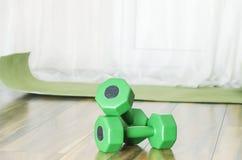 Pesas de gimnasia verdes y estera para el entrenamiento interior Concepto de entrenamiento en casa y consiguiendo más fuerte imagen de archivo libre de regalías