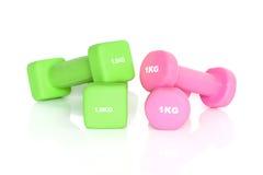 Pesas de gimnasia verdes y rosadas de la aptitud Imágenes de archivo libres de regalías
