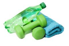 Pesas de gimnasia y botella de agua, toalla Fotografía de archivo libre de regalías