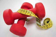 Pesas de gimnasia y cinta métrica Imagen de archivo