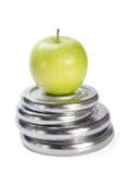 Pesas de gimnasia y fondo verde del blanco del onr de la manzana imágenes de archivo libres de regalías