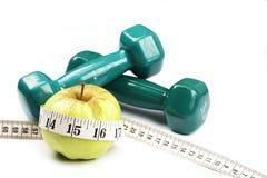 Pesas de gimnasia y la manzana con la cinta de medición Imagen de archivo libre de regalías