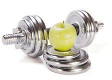 Pesas de gimnasia y manzana verde en el fondo blanco imagen de archivo libre de regalías