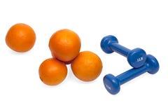 Pesas de gimnasia y naranjas Foto de archivo libre de regalías