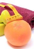 Pesas de gimnasia y toalla para usar en aptitud, fruta fresca con cinta métrica Fotografía de archivo libre de regalías