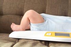 Pesatura del neonato sulla scala Immagini Stock