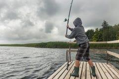 Pesca adolescente del muchacho en el embarcadero de madera Imagen de archivo libre de regalías