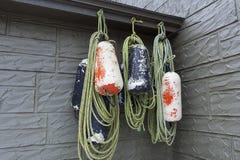 A pesca alaranjada e azul da espuma pintada buoys a suspensão nos ganchos fotografia de stock