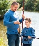 Pesca amigável do pai e do filho com hastes imagens de stock