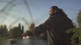 Pesca barbuta del pescatore sul fiume Fisher sta sulla sponda del fiume con la barretta stock footage