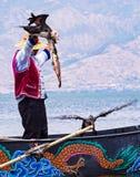 Pesca china del hombre con los pájaros de los cormoranes en el lago Erhai - Yunnan, China Foto de archivo