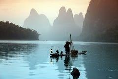 Pesca chinesa do homem com pássaros dos cormorões Imagem de Stock