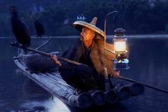 Pesca chinesa do homem com pássaros dos cormorões dentro Imagens de Stock Royalty Free
