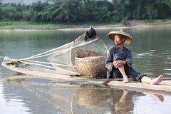 Pesca cinese dell'uomo con gli uccelli dei cormorani dentro Immagine Stock