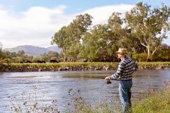 Pesca com mosca do aposentado em um rio imagens de stock