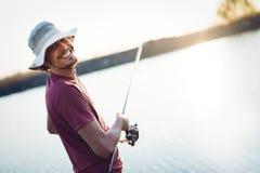 Pesca como reconstrucción y deportes exhibidos por el pescador en el lago Imagen de archivo libre de regalías