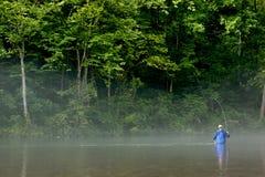 Pesca con la mosca del pescatore in un fiume nebbioso Fotografie Stock Libere da Diritti