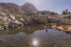 Pesca con mosca de la mujer en el lago de la montaña Fotografía de archivo