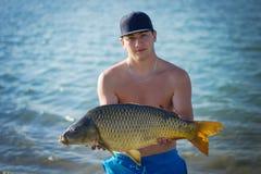 Pesca da carpa Pescador novo que guarda uma carpa comum grande no lago Feche acima do retrato imagem de stock