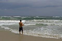 Pesca da costa do homem durante a tempestade Foto de Stock Royalty Free