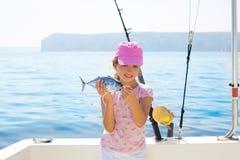 A pesca da menina da criança no barco que guardara atuns pequenos pesca o catc Foto de Stock