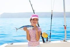 A pesca da menina da criança no barco que guardara atuns pequenos pesca o catc Foto de Stock Royalty Free