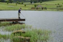 Pesca da perda do menino na represa ou no cais do lago Imagens de Stock