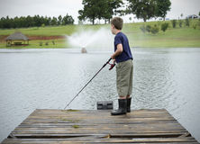 Pesca da perda do menino na represa ou no cais do lago Foto de Stock