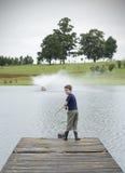 Pesca da perda do menino no cais do lago Imagens de Stock