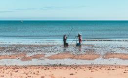 Pesca de dos hombres en la playa de Hornsea fotos de archivo