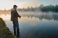 Pesca de Fisher no nascer do sol nevoento fotografia de stock